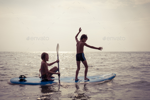 Happy children playing on the beach at the day time. - Stock Photo - Images