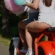 Two Beautiful Girls in Denim Shorts Ride in the Park on an Electric Scooter in the Summer in  Rea - VideoHive Item for Sale