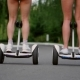 View of the Back Legs of the Girls in Short Shorts Riding GyroScooter on a Sunny Summer Day - VideoHive Item for Sale