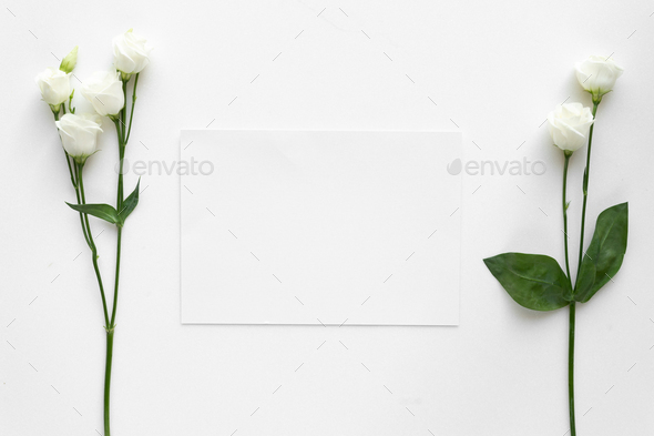 Wedding invitation card with roses, on white marble. Top view. - Stock Photo - Images