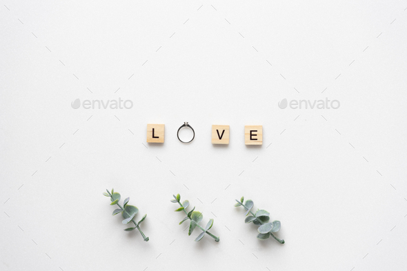 Wooden letters with engagement ring spelling love, with oregano - Stock Photo - Images