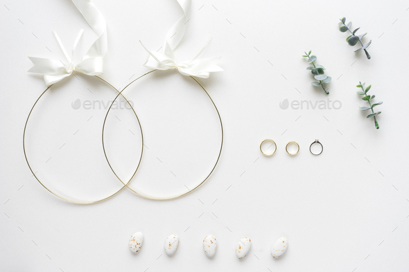 Wedding crowns, rings,  oregano branches and candy on white marb - Stock Photo - Images
