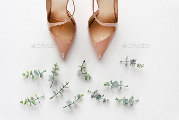 Bridal shoes with oregano branches on white marble. Top view. - Stock Photo - Images