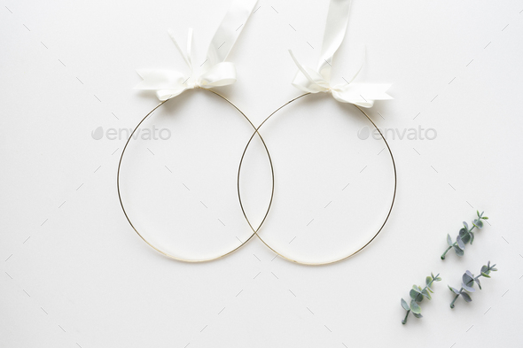 Wedding crowns and oregano branches on white marble. Top view. - Stock Photo - Images