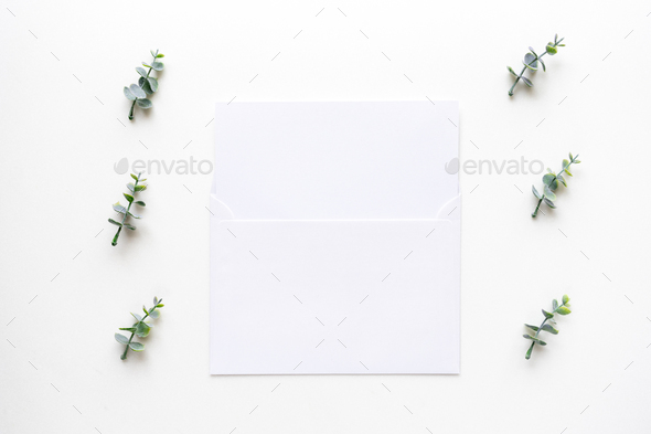Wedding invitation card and oregano branches on white marble. To - Stock Photo - Images