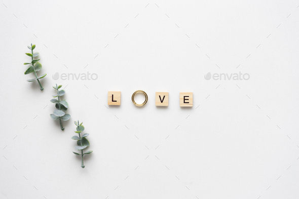 Wooden letters and wedding rings spelling love, with candies and - Stock Photo - Images