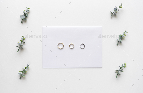 Wedding invitation card on white marble with wedding rings and o - Stock Photo - Images