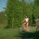 Beautiful Girls on Bicycles on the Background of Green Trees in a Sunny Day in the Park - VideoHive Item for Sale