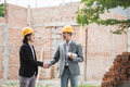 designers discussing construction plan shaking hand - PhotoDune Item for Sale