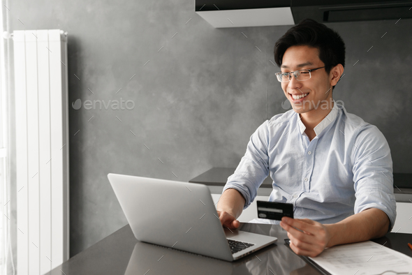 Portrait of a smiling young asian man - Stock Photo - Images