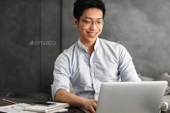 Happy young asian man using laptop computer - Stock Photo - Images
