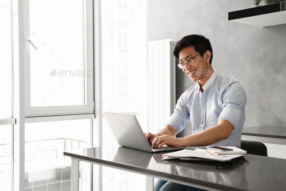 Portrait of a happy young asian man using laptop computer - Stock Photo - Images