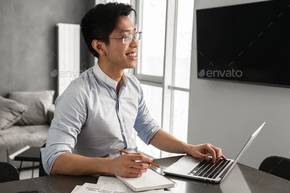 Portrait of a cheerful young asian man using laptop - Stock Photo - Images