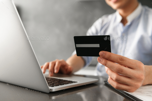 Close up of a man holding plastic credit card - Stock Photo - Images