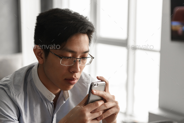 Portrait of a concentrated young asian man - Stock Photo - Images