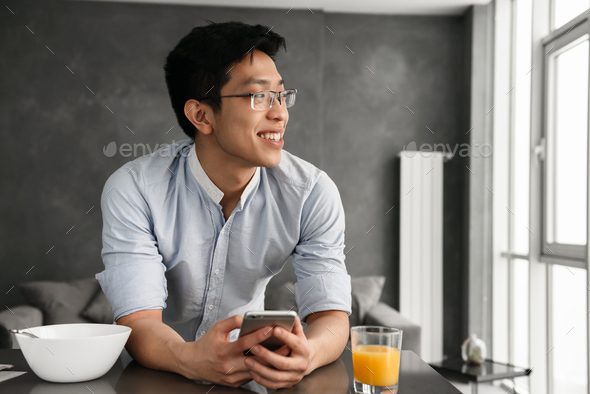 Portrait of a satisfied young asian man - Stock Photo - Images