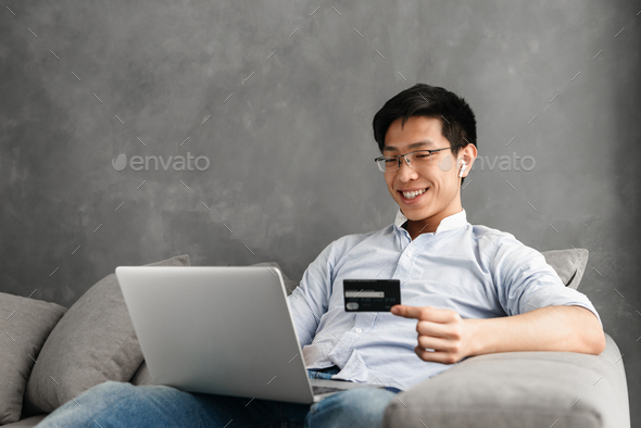 Happy young asian man using laptop - Stock Photo - Images