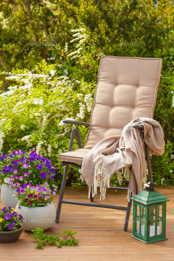 garden chair on terrace and pansy flowers - Stock Photo - Images