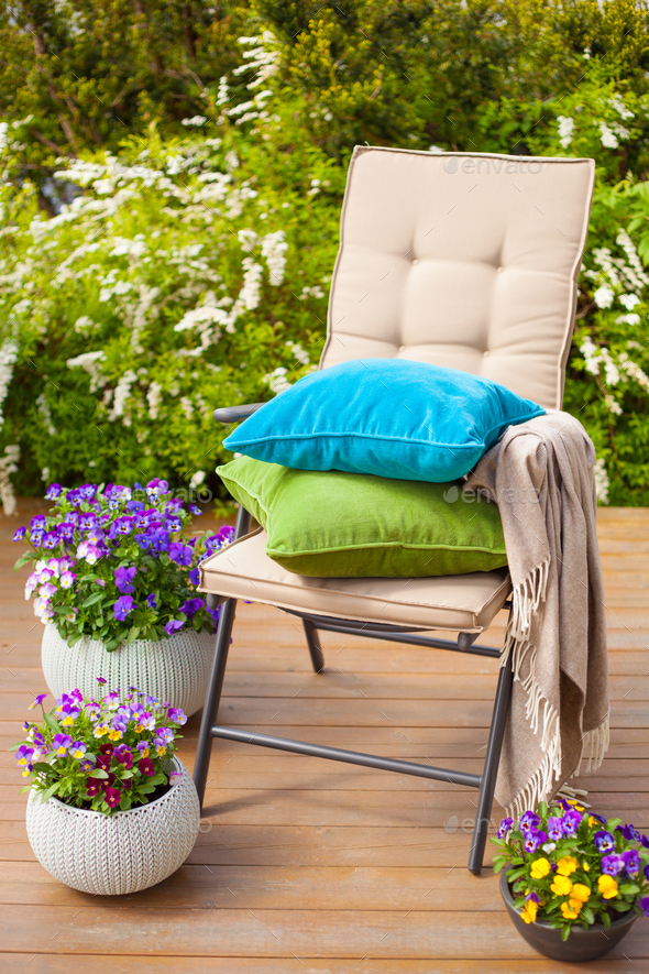 garden chair on terrace in sunlight, flowers bush - Stock Photo - Images