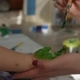 Woman Paints with Brush on Baby Hand for Making Green Handprints.  Shot - VideoHive Item for Sale