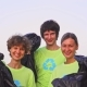 Five Young Volunteers in Green T-shirts with Recycle Image Collect Garbage on an Ocean Beach - VideoHive Item for Sale