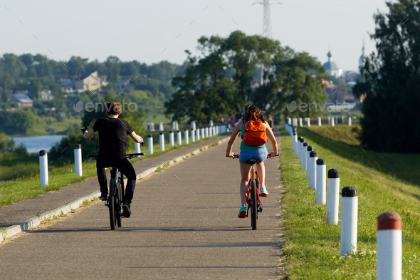 The girl and the young man ride on a bicycle in the city - Stock Photo - Images