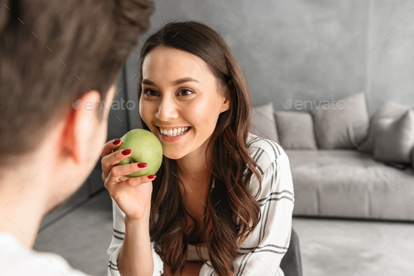 Image of attractive smiling woman looking at man, while sitting - Stock Photo - Images