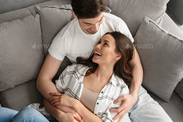 Photo of happy atractive man and woman smiling, and hugging whil - Stock Photo - Images