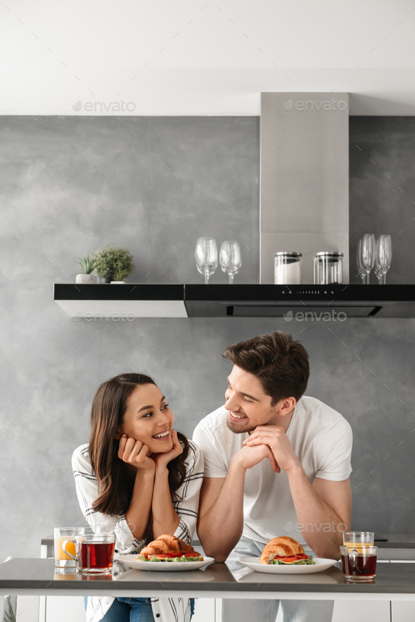 Portait of happy couple looking at each other and smiling, while - Stock Photo - Images