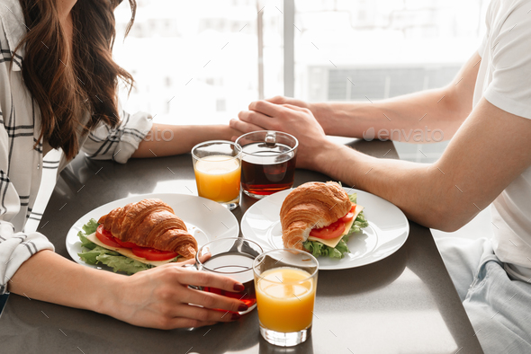 Image cropped of caucasian man and woman having breakfast, or di - Stock Photo - Images