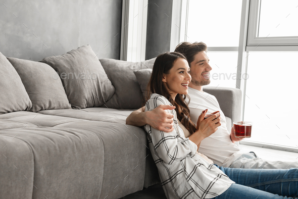 Image of attractive man hugging happy woman, while sitting on fl - Stock Photo - Images
