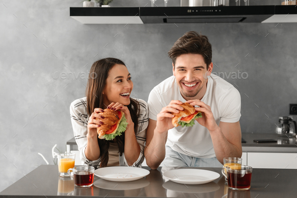 Young and beautiful couple smiling, and eating sandwiches on bre - Stock Photo - Images