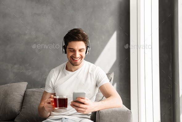 Portrait of brunette man 30s in earphones sitting on sofa indoor - Stock Photo - Images
