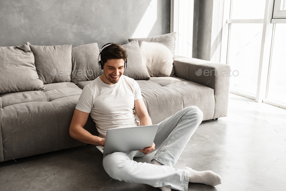 Joyful man 30s in basic clothing sitting on floor at home, and l - Stock Photo - Images