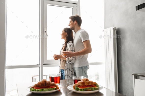 Married couple smiling, and looking through big window, while ha - Stock Photo - Images
