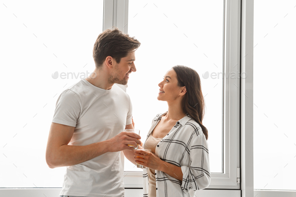 Married couple smiling, and looking at each other while standing - Stock Photo - Images