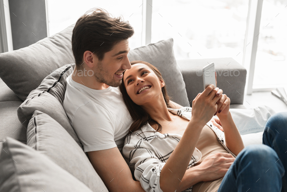 Happy family portrait of positive family lying together on sofa - Stock Photo - Images