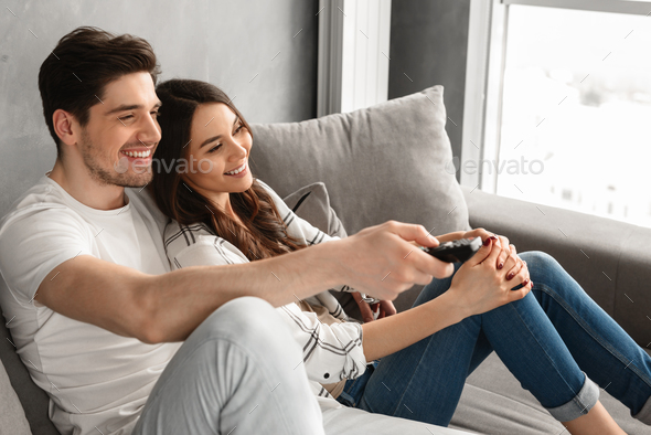 Image of happy man and woman sitting on sofa at home and watchin - Stock Photo - Images