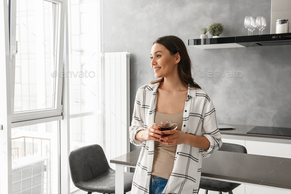 Gorgeous woman in casual wear looking aside with happy smile, an - Stock Photo - Images