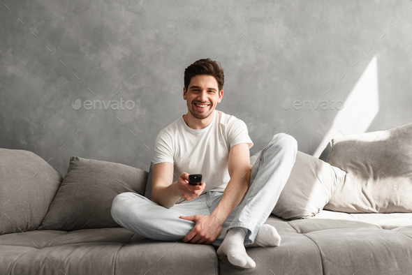 Photo of joyful man 30s in casual clothing sitting on sofa in li - Stock Photo - Images