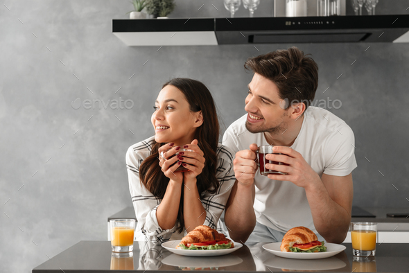 Young and beautiful couple looking aside and smiling, while havi - Stock Photo - Images