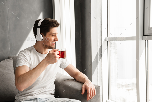 Photo in of pleased man looking through window and listening to - Stock Photo - Images