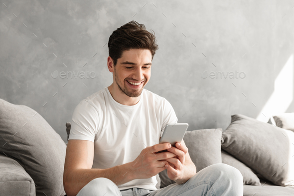 Handsome man in basic t-shirt smiling and holding mobile phone i - Stock Photo - Images