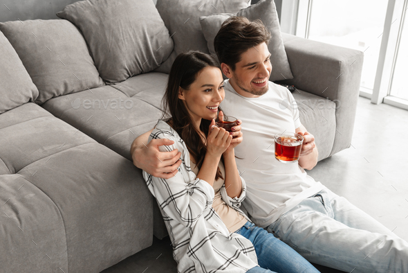 Image of happy couple sitting on floor near sofa at home and loo - Stock Photo - Images