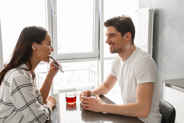 Image of attractive man and woman looking at each other, while s - Stock Photo - Images
