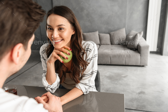 Photo of beautiful smiling woman looking at man and holding his - Stock Photo - Images