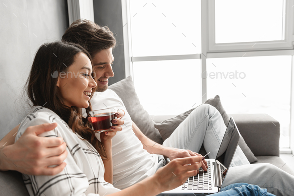 Married couple man and woman sitting on sofa in apartment near b - Stock Photo - Images