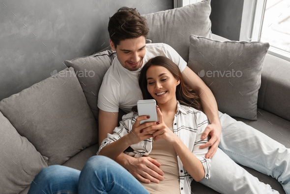 Caucasian couple man and woman in casual clothing resting in liv - Stock Photo - Images