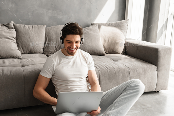 Happy guy with dark hair sitting on floor indoor, and listening - Stock Photo - Images