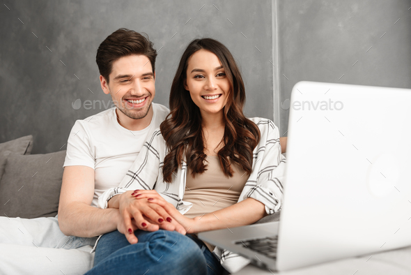 Happy family man and woman sitting together on couch indoor, and - Stock Photo - Images